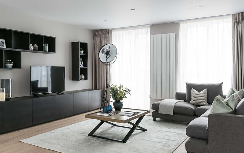living room with tv and shelving near a black lamp and dark beige sofas